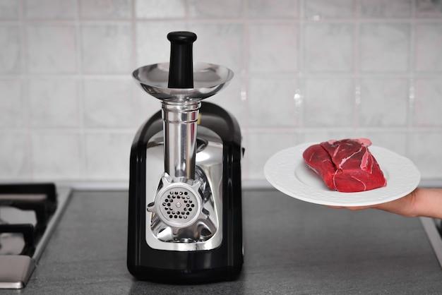 Maszynka do mięsa ze świeżym mięsem na stole we wnętrzu kuchni