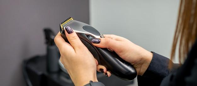 Maszynka do strzyżenia włosów w rękach kobiet profesjonalny fryzjer lub fryzjer w salonie fryzjerskim