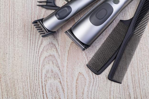 Maszynka do włosów z grzebieniem na drewnianym tle