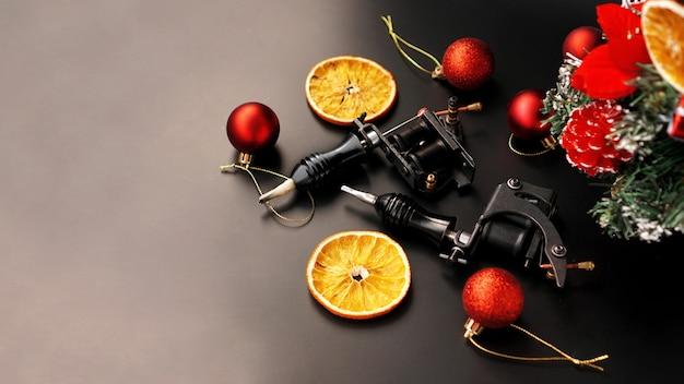 Maszynki do tatuażu na świątecznym tle - świąteczny wystrój z drzewem na tle blsck