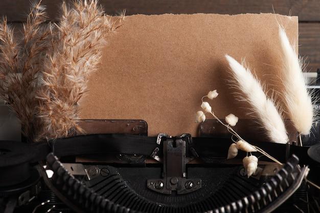 Maszyny do pisania z bliska i suszone kwiaty. vintage papier stonowany i kraft