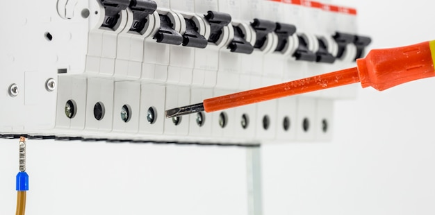 Maszyny elektryczne, przełączniki, na białym tle na biały, zbliżenie, podłącz kabel znacznika do urządzenia za pomocą czerwonego śrubokręta