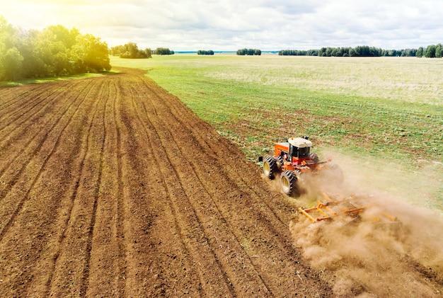 Maszyny rolnicze do zbioru upraw na polach. ciągnik ciągnie mechanizm do sianokosów. zbiór jesienią rano o świcie. agrobiznes w regionie ałtaju rosja. widok z lotu ptaka z góry