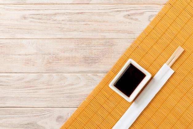 Mata bambusowa i sos sojowy z pałeczkami sushi na drewnianym stole. widok z góry z miejsca na kopię do sushi. leżał płasko