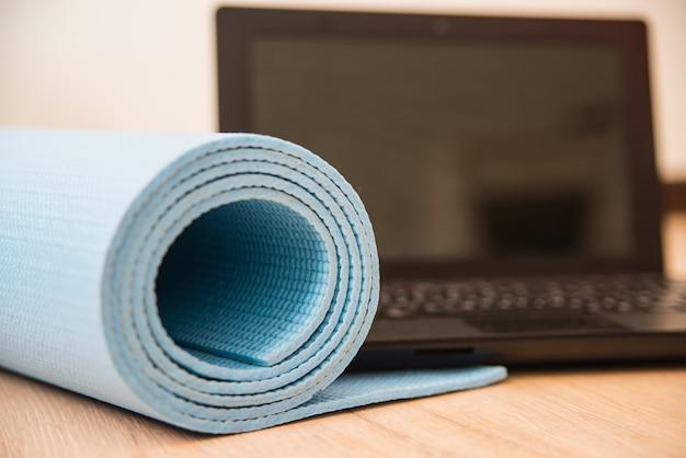 Mata do jogi i laptop na podłodze. fitness w domu podczas kwarantanny lub dla freelancerów