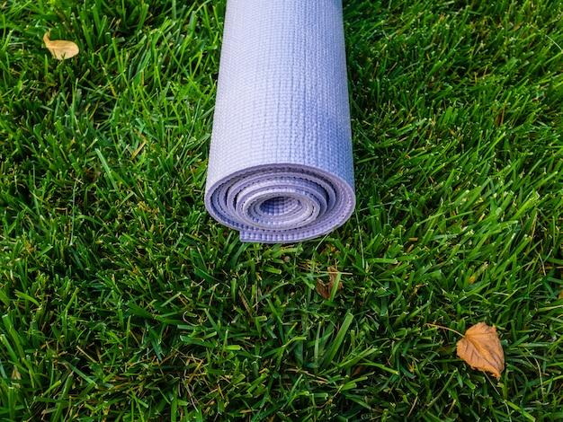 Mata do jogi lub fitnessu. purpurowy dywanik na zielonej trawie w cieniu drzewa