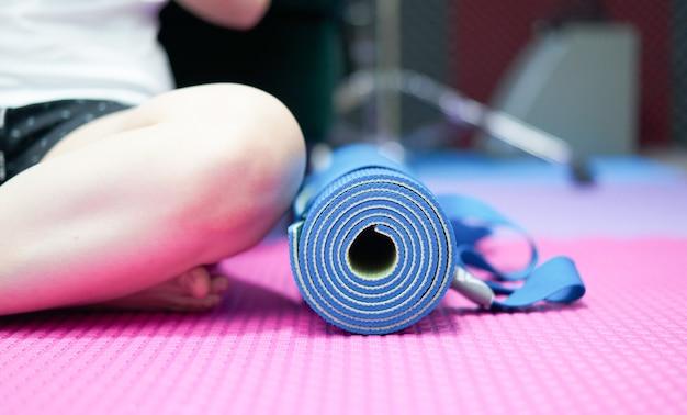 Mata do jogi na podłodze obok siedzieć ze skrzyżowanymi nogami przykucnąć na podłodze w domu w stroju sportowym