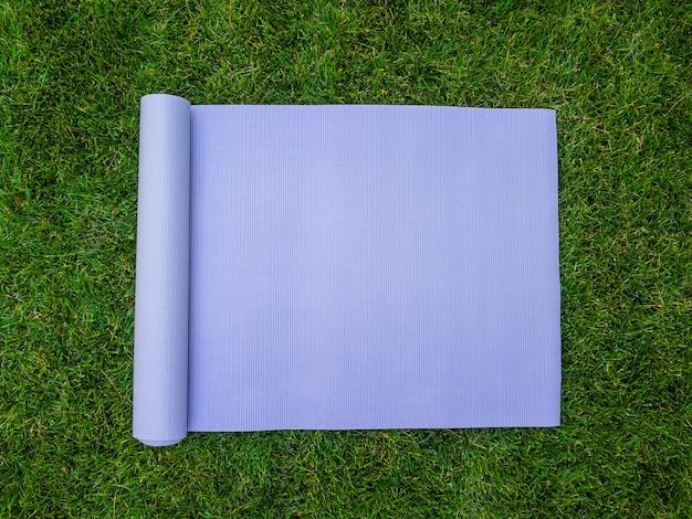 Mata do jogi, pilates lub fitness na zielonym trawniku. trening na świeżym powietrzu