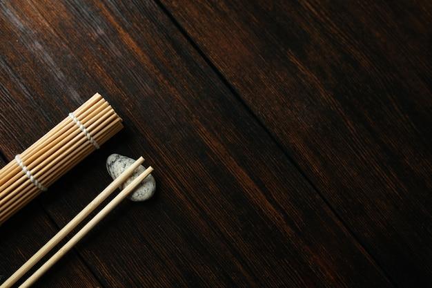 Mata na bułki i pałeczki do chińskich azjatyckich potraw na ciemnym drewnianym tle