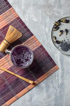 Matcha blue grochowy napój na jasnoszarym stole.