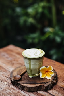 Matcha latte w przezroczystym szkle z kwiatkiem
