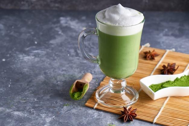 Matcha latte z mlekiem migdałowym i śmietaną w szkle na szarym kamiennym stole