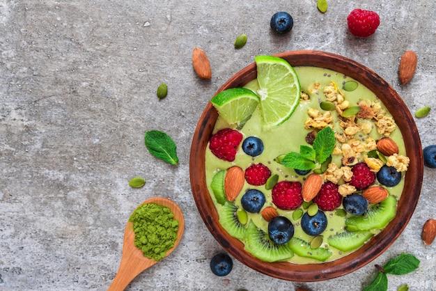 Matcha miska z zieloną herbatą i świeżymi owocami, jagodami, orzechami, ziarnami i muesli na zdrowe śniadanie wegetariańskie
