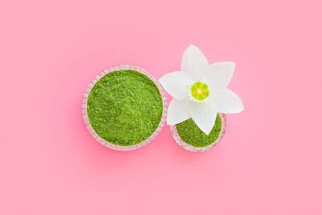 Matcha suchy zielony proszek na różowej powierzchni do robienia japońskiej naturalnej herbaty.