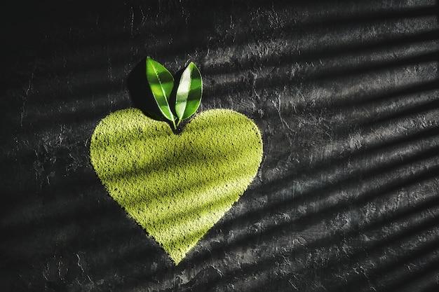 Matcha w proszku w kształcie serca na ciemnym tle z miejsca na kopię.