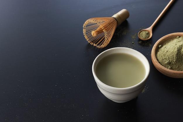 Matcha zielona herbata latte na czarnym stole