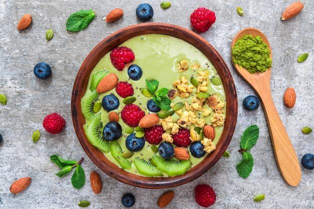 Matcha zielona miska na smoothie ze świeżymi owocami, jagodami, orzechami, ziarnami i muesli z łyżką do zdrowego śniadania