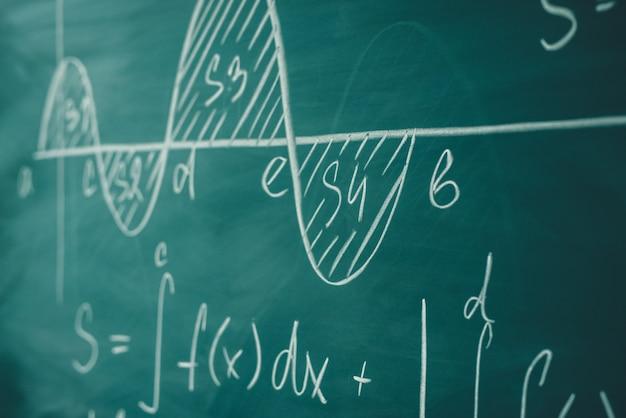Matematyka funkcja całki formuły grafowe na tablicy.
