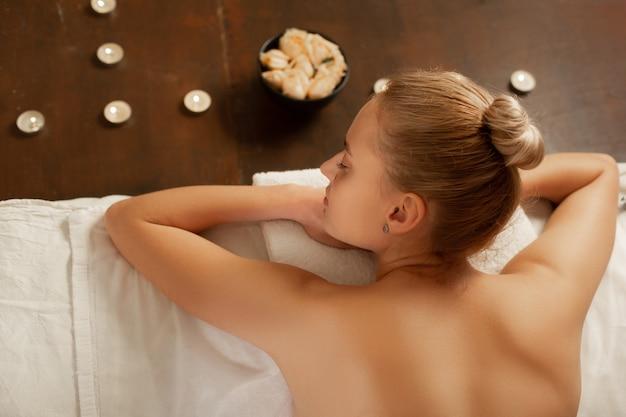 Materac w szafce. spokojna młoda dama ze związanymi włosami leżąca na zadaszonym łóżku do masażu otoczona kwiatami i świecami