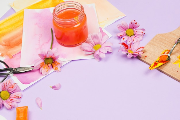 Materiały artystyczne, fioletowe kwiaty i szklanki na fioletowym stole
