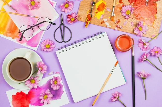 Materiały artystyczne, fioletowe kwiaty, pusty notatnik i szklanki na fioletowym stole