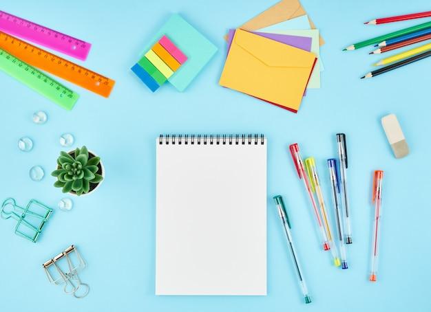 Materiały biurowe, artykuły papiernicze na niebieskim biurku biurowym. widok z góry z notesu.