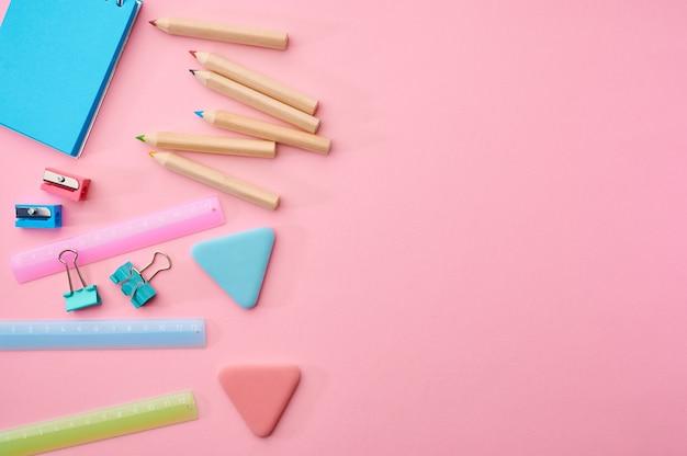 Materiały biurowe dostarcza zbliżenie, różowe tło. akcesoria szkolne lub edukacyjne, przybory do pisania i rysowania, ołówki i gumki, linijka i spinacze do papieru