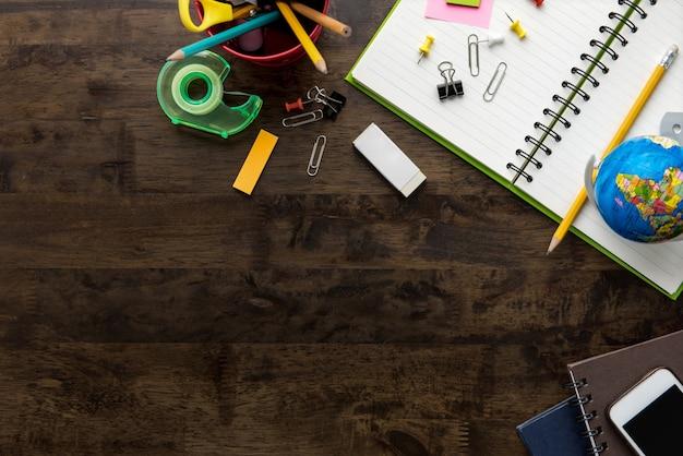 Materiały biurowe i materiały edukacyjne na tle ciemnego brązu drewniany stół