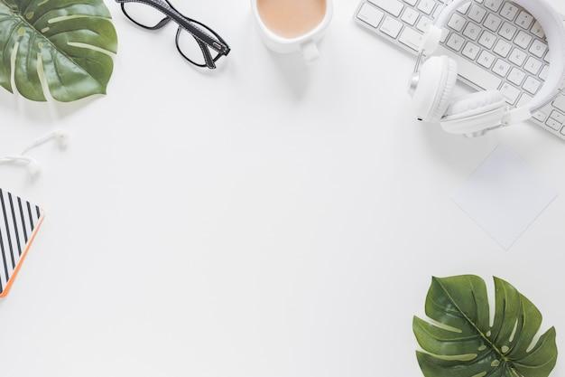 Materiały biurowe i urządzenia na białym biurku ozdobione liśćmi