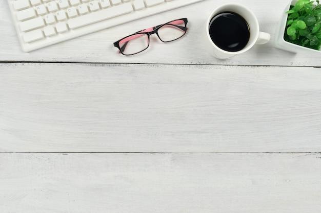 Materiały biurowe (kawa, laptop, okulary) na biały drewniany.