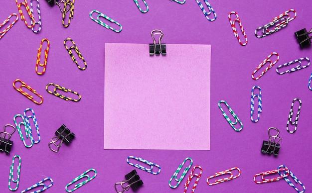 Materiały biurowe. kolorowy papier notatek, spinacz do papieru na fioletowym tle.