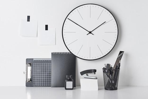 Materiały biurowe, lepki i okrągły zegar na białym tle