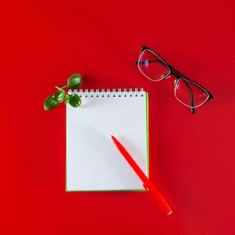 Materiały biurowe na czerwonym tle pusty notatnik, długopis i okulary