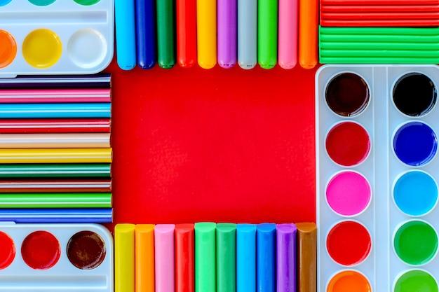 Materiały biurowe na czerwonym tle. różne przybory szkolne na jasnym czerwonym tle.