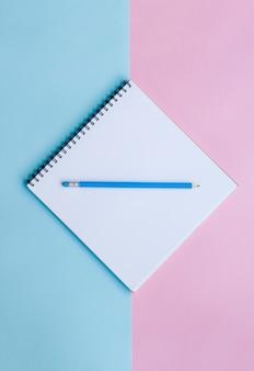 Materiały biurowe na różowym i niebieskim tle. praca w domu.