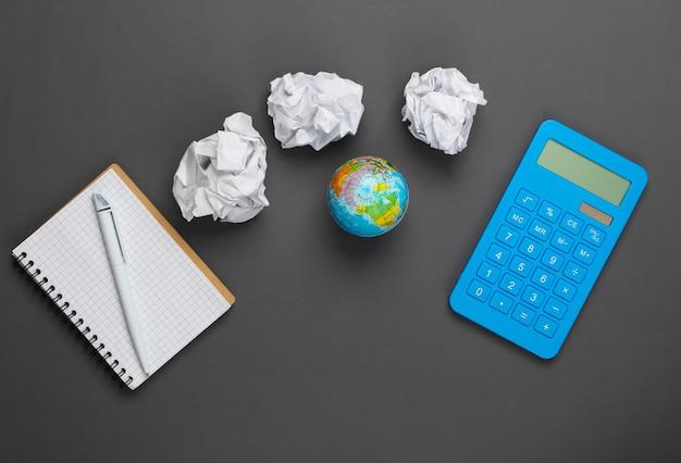 Materiały biurowe na szaro. kalkulator, zmięte papierowe kulki, globus, notatnik