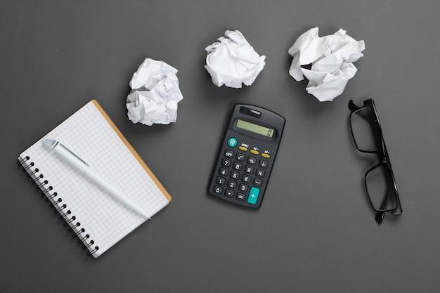 Materiały biurowe na szaro. kalkulator, zmięte papierowe kulki, notes