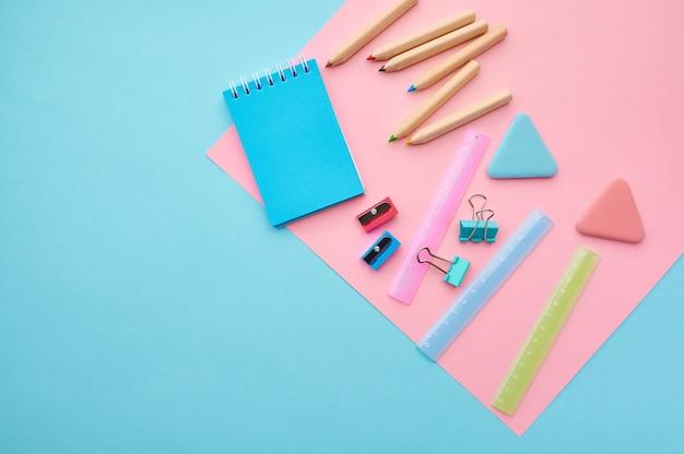 Materiały biurowe, niebieskie i różowe tło. akcesoria szkolne lub edukacyjne, przybory do pisania i rysowania, ołówki i gumki, linijka i spinacze do papieru