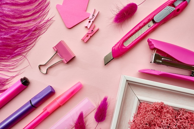 Materiały biurowe, różowe tło. akcesoria szkolne lub edukacyjne, przybory do pisania i rysowania, ołówki i linijka, zszywacz i długopisy