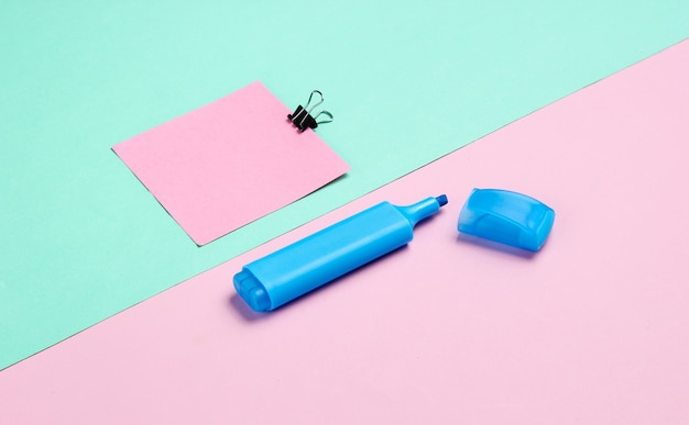 Materiały biurowe. spinacz do papieru, pisak, kartka papieru notatki na różowym niebieskim pastelowym tle