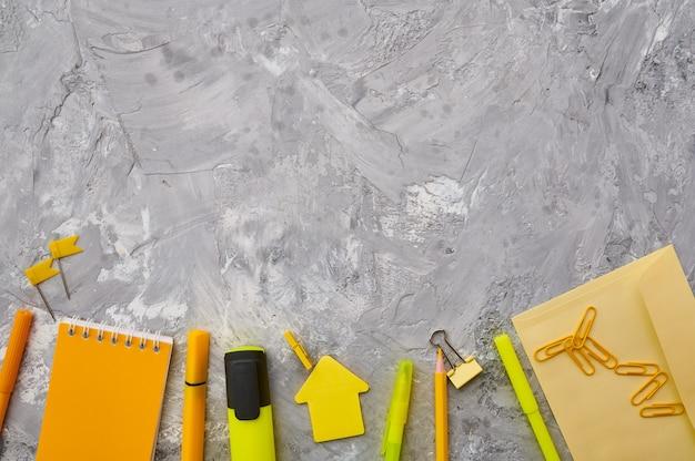 Materiały biurowe w żółtych odcieniach zbliżenie, marmurowe tło. akcesoria szkolne lub edukacyjne, przybory do pisania i rysowania, ołówki i gumki itp.