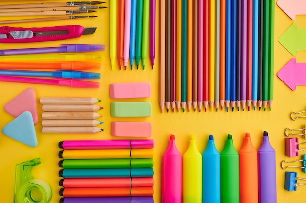 Materiały biurowe, żółte tło. akcesoria szkolne lub edukacyjne, przybory do pisania i rysowania, ołówki i gumki, pędzle i długopisy