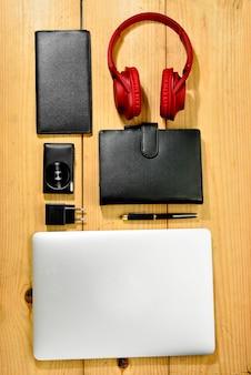 Materiały biznesmen, takie jak laptop, aparat fotograficzny, portfel, notatnik i słuchawki do pracy
