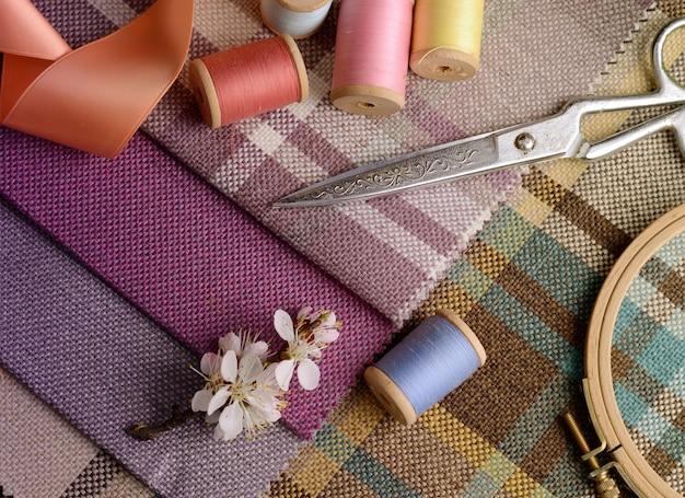 Materiały do szycia, igły, nożyczki w stylu vintage na kolorowej tkaninie z brązu