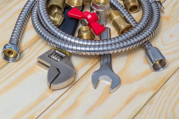 Materiały hydrauliczne, kran, narzędzia, armatura i wąż na drewnianych deskach są używane do wymiany lub naprawy