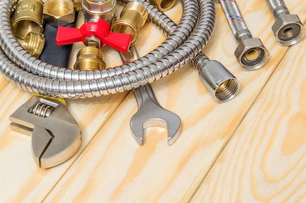 Materiały hydrauliczne, kran, narzędzie i wąż na drewnianych deskach są używane do wymiany lub naprawy