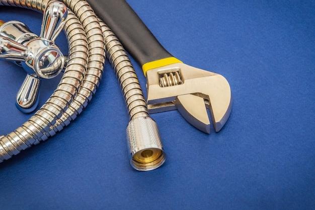 Materiały hydrauliczne kran, narzędzie i wąż na niebieskim tle służą do wymiany pod prysznicem