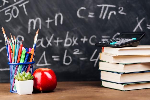 Materiały i brogować książki umieszczać na biurku na chalkboard tle