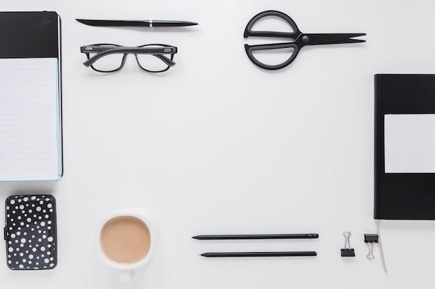 Materiały i filiżanka kawy w pobliżu szklanki na białym stole