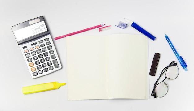 Materiały lub biurowy wyposażenie na białym tle. notebook z pustą pozycją środkową.